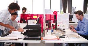 Gente que trabaja en los escritorios en oficina abierta moderna del plan almacen de video