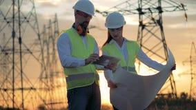 Gente que trabaja en una línea eléctrica, mirada en una tableta 4K almacen de video