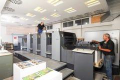 Gente que trabaja en una máquina de impresión en offset fotos de archivo libres de regalías