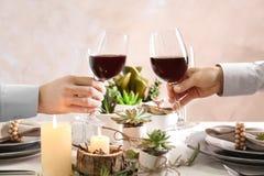 Gente que tuesta con los vidrios de vino rojo Fotografía de archivo