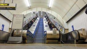 Gente que usa las escaleras móviles en la estación del metro Londres Imagenes de archivo