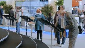 Gente que usa pantallas táctiles interactivas en la exposición urbana almacen de video