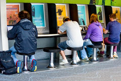 Gente que usa una estación de carga del ordenador portátil en un aeropuerto Imágenes de archivo libres de regalías