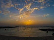 Gente que va para una nadada en la puesta del sol en una laguna atlántica en el verano Fotos de archivo