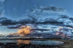 Gente que va para una nadada en la puesta del sol en una laguna atlántica en el verano Fotografía de archivo