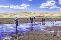 Gente que vadea la corriente en grandes dunas de arena Imagen de archivo