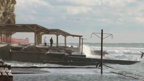 Gente que ve en la tormenta del mar Ondas potentes enormes que se rompen en el malecón en tormenta severa importante Rusia, ciuda almacen de metraje de vídeo