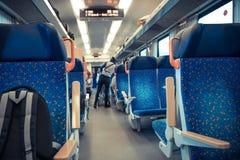 Gente que viaja en tren Est?n conduciendo en un carro y un cup? Trabajo, respeto, compro los refrigerios, escucho la m?sica El es imagen de archivo libre de regalías