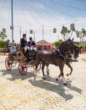 Gente que viaja en un carro traído por caballo en la Sevilla favorablemente Imágenes de archivo libres de regalías