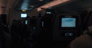 Gente que viaja por el blane en la noche Cabina oscura con los monitores de trabajo del asiento metrajes