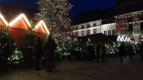 Gente que visita un mercado de la Navidad en la noche Imágenes de archivo libres de regalías