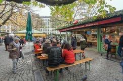 Gente relajante con la cerveza y la comida rápida en la muchedumbre de visitantes hambrientos de Viktualienmarkt Imagen de archivo libre de regalías