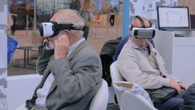 Gente senior che per mezzo della cuffia avricolare di realtà virtuale archivi video