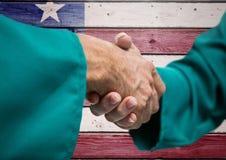 Gente senior che stringe le loro mani contro la bandiera americana Fotografie Stock Libere da Diritti