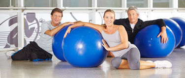 Gente senior con le palle della palestra che si siedono nel centro di forma fisica Immagini Stock