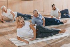 gente senior sorridente che si prepara sulle stuoie di yoga immagine stock