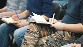 Gente - sentándose y escuche la conferencia o la presentación, taller, clase principal - notas y plumas almacen de metraje de vídeo