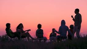 Gente sentada en la playa con fogata al atardecer almacen de video