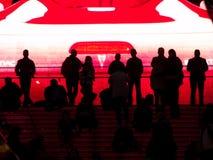 Gente silueteada contra la pantalla video enorme. Imágenes de archivo libres de regalías