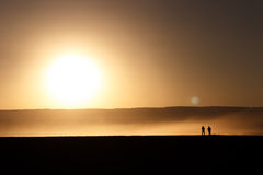 Gente silueteada en la puesta del sol imágenes de archivo libres de regalías
