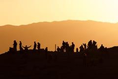 Gente silueteada en la puesta del sol fotos de archivo