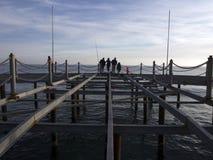 Gente silueteada en un embarcadero de la pesca en la puesta del sol Imagenes de archivo