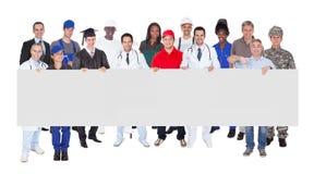Gente sonriente con los diversos empleos que sostienen la cartelera en blanco fotografía de archivo libre de regalías