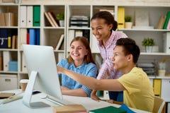 Gente sonriente que trabaja con el ordenador Foto de archivo libre de regalías