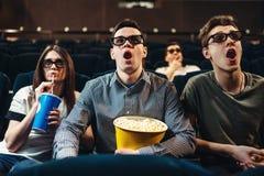 Gente sorprendida en los vidrios 3d que mira película Fotografía de archivo