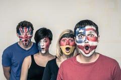 Gente sorpresa con le bandiere sui fronti Fotografie Stock Libere da Diritti