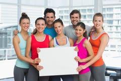 Gente sorridente adatta che tiene bordo in bianco Fotografie Stock Libere da Diritti