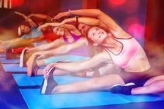 Gente sorridente che fa allungando esercizio in palestra Immagine Stock