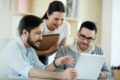 Gente sorridente che lavora con il computer portatile Immagine Stock
