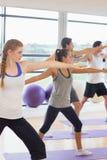 Gente sportiva che allunga le mani alla classe di yoga nello studio di forma fisica Immagini Stock