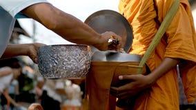 Gente tailandesa que ofrece el arroz cocinado al monje budista el madrugada almacen de video