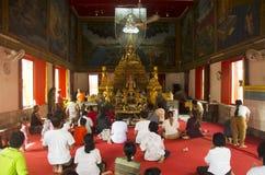 Gente tailandesa que ruega la estatua de Buda en fes prestados tradicionales de la vela Foto de archivo