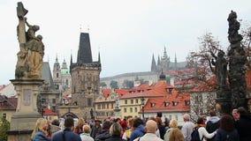 Gente turística en Charles Bridge en Praga, edificios viejos de la ciudad almacen de metraje de vídeo