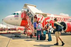 Gente turística internacional que sube al vuelo de Air Asia en el aeropuerto de Bangkok
