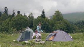 Gente turística que come y que bebe mientras que verano que acampa en paisaje de la montaña almacen de video