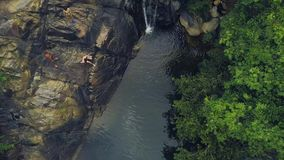 Gente turistica che si tuffa e che nuota in cascata della montagna nel paesaggio aereo della foresta pluviale La gente che salta  stock footage