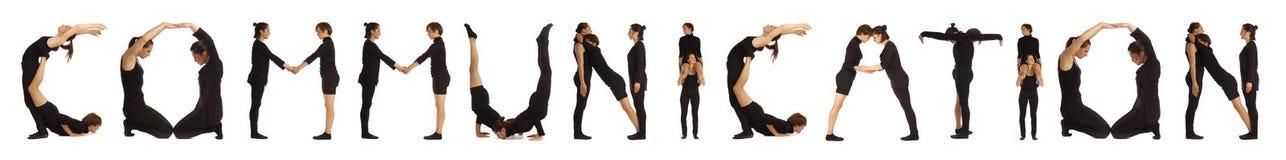 Gente vestida negro que forma palabra de la COMUNICACIÓN imagenes de archivo