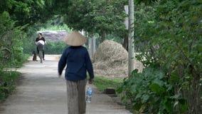 Gente vietnamita que camina y que completa un ciclo en la calle del AMI Châu almacen de video