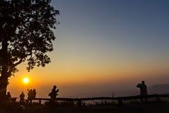 Gente y árboles silueteados con puesta del sol Imágenes de archivo libres de regalías