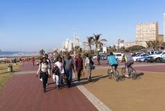 Gente y ciclistas en la 'promenade' en frente de la playa Imagenes de archivo