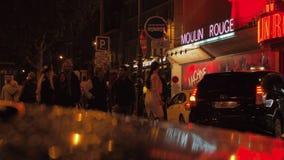 Gente y coches en calle de la noche con Moulin Rouge famoso, París almacen de video