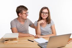 Gente y concepto de la educación - dos estudiantes divertidos felices que se sientan en la tabla de madera con el ordenador portá fotografía de archivo libre de regalías