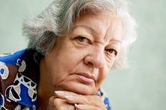 Retrato de la mujer mayor seria que mira la cámara con las manos en el ch Imagenes de archivo