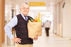 Gentelman in einem Einkaufszentrum, das einen Papierbeutel anhält Lizenzfreie Stockfotografie