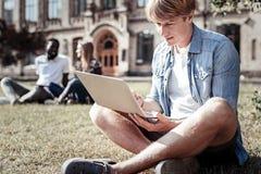 Gentil étudiant bel tenant un ordinateur portable Photo libre de droits
