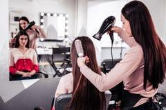 Gentil coiffeur professionnel employant un hairdryer puissant image stock